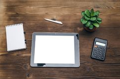 Tablet computer with blank screen. Business ideas concept. Mobile tablet computer with copy space, calculator and notepad with blank pages on wooden office desk Royalty Free Stock Photos