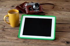 Tablet computer with a blank screen, cup of coffee, camera Stock Photography