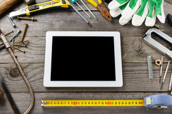 Tablet computer with a blank screen with old tools. Tablet computer with a blank screen on a wooden table in the workshop with old tools, top view stock photography