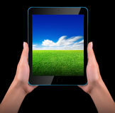 Tablet computer with blue sky and green grass Royalty Free Stock Photography
