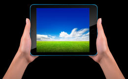 Tablet computer with blue sky and green grass Stock Photography