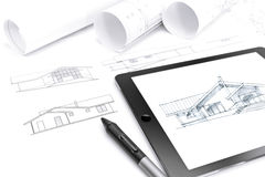 Tablet computer with blueprint and rolls of plans Stock Photography