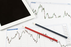 Tablet computer, Blueprints, charts and red blue pencils on a white background, business concept. Stock Photos