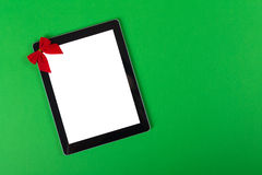 Tablet computer with a bow on green background Royalty Free Stock Photography