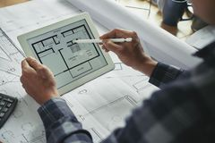 Examining building plan. Tablet computer with building plan in hands of architect royalty free stock photo