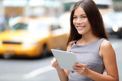Tablet computer business woman in New York City. Standing in street with yellow taxi cab. Beautiful young professional businesswoman smiling happy. Mixed race Royalty Free Stock Image