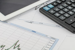Tablet computer, calculator and business graph on white background Royalty Free Stock Images