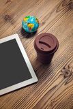 Tablet computer, coffee cup and globe on wood table Stock Images