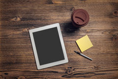 Tablet computer, coffee cup, pen and sticky paper on wood table Royalty Free Stock Image