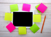 Tablet computer with colorful sheets of paper on wooden backgrou Stock Photo