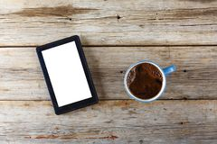 Tablet computer and a cup of black coffee on a wooden table. View from above Royalty Free Stock Photos