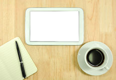 Tablet computer and a cup of coffee on the desk Royalty Free Stock Image