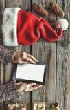 Tablet-Computer in den menschlichen Händen Nahe der Tabelle mit Tablet-Computer-Geschenkboxen, Weihnachtsglocke und flaumigen Tan Stockbilder