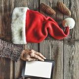 Tablet-Computer in den menschlichen Händen Nahe der Tabelle mit Tablet-Computer-Geschenkboxen, Weihnachtsglocke und flaumigen Tan Stockfotos