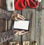 Tablet-Computer in den menschlichen Händen Nahe der Tabelle mit Tablet-Computer-Geschenkboxen, Weihnachtsglocke und flaumigen Tan Lizenzfreie Stockbilder