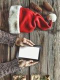 Tablet-Computer in den menschlichen Händen Nahe der Tabelle mit Tablet-Computer-Geschenkboxen, Weihnachtsglocke und flaumigen Tan Lizenzfreie Stockfotografie