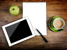 Tablet computer. Tablet with an empty screen close to a pen and green cup and apple Stock Images