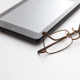 Tablet computer and eyeglasses Stock Image