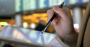 Tablet computer is a friend in any travel. Close-up shot of a woman at the airport working with touch pad using pen. Defocused flight schedule in background stock video