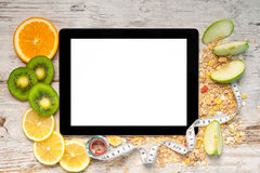 Tablet computer with fruit and a measuring tape for weight loss Royalty Free Stock Photo
