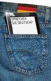 Tablet Computer - German Everywhere. Blue jeans fabric with black tablet computer with phrase Sprechen Sie Deutsch? in a pocket and label with German flag Stock Photography