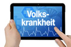 Tablet computer with the german word for widespread disease - volkskrankheit. Isolated on white background stock photography