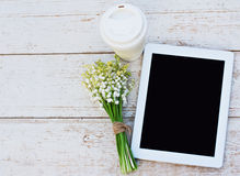 Tablet computer, a glass of coffee and  lilies of valley Stock Photography