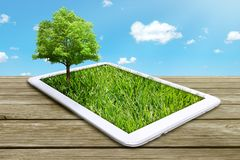 Tablet computer with green grass and tree. Growing on a screen isolated on blue sky  background Royalty Free Stock Images