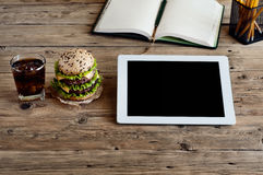 Tablet computer with a hamburger and a glass of cola Royalty Free Stock Image