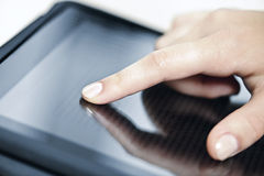 Tablet computer with hand. Female hand touching tablet computer screen with finger Stock Images
