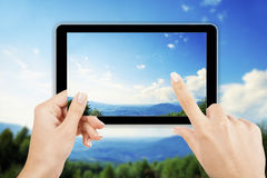 Tablet computer. In hand on the forest backgrounds Stock Image