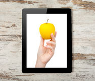 Tablet computer with the hand and yellow apple Royalty Free Stock Image
