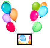 Tablet computer hanging on color balloons Royalty Free Stock Photo