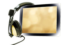 Tablet computer with headphones. On a white background Royalty Free Stock Photography