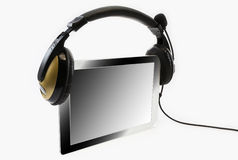 Tablet computer with headphones. On a white background Royalty Free Stock Photos