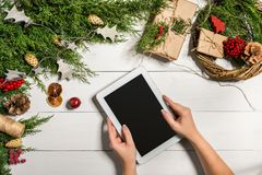 Tablet computer in the human hands. Near the table with tablet computer gift box, christmas bell and fluffy fir branches Royalty Free Stock Image