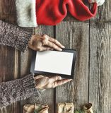 Tablet computer in the human hands. Near the table with tablet computer gift boxes, christmas bell and fluffy fir branches. Free s Royalty Free Stock Images
