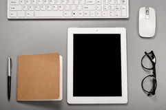 Tablet computer with a keyboard, computer mouse, pen and notepad Royalty Free Stock Photos