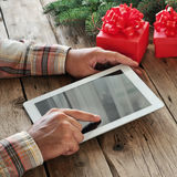 Tablet computer in men hands. Near the table with tablet compute Stock Image