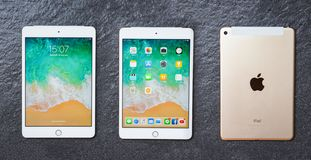 Tablet computer New Apple iPad mini white gold color with display screen front and Apple logo back stock photo