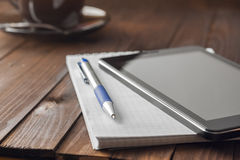 Tablet computer is on notepad with a pen Royalty Free Stock Images