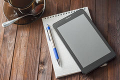 Tablet computer is on notepad with a pen, Royalty Free Stock Image