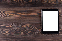 Tablet computer on the old wooden boards. White screen. Top view Royalty Free Stock Images