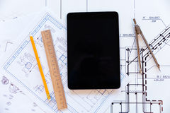 Tablet computer and paper with blueprints Stock Photos
