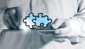 Tablet computer and pixel puzzle. Close up of a man using tablet computer and pixel puzzle as partnership concept Stock Photo