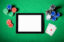 Tablet computer on poker table Stock Photography