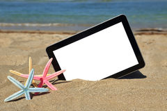 Tablet computer. On sandy beach Royalty Free Stock Image