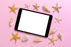 Tablet computer with seashells on pink background. technology vacation holidays concept stock photo