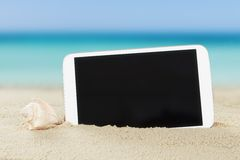 Tablet computer and shell on sand Royalty Free Stock Image