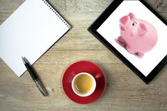Tablet computer showing piggy bank and notepad Royalty Free Stock Photo